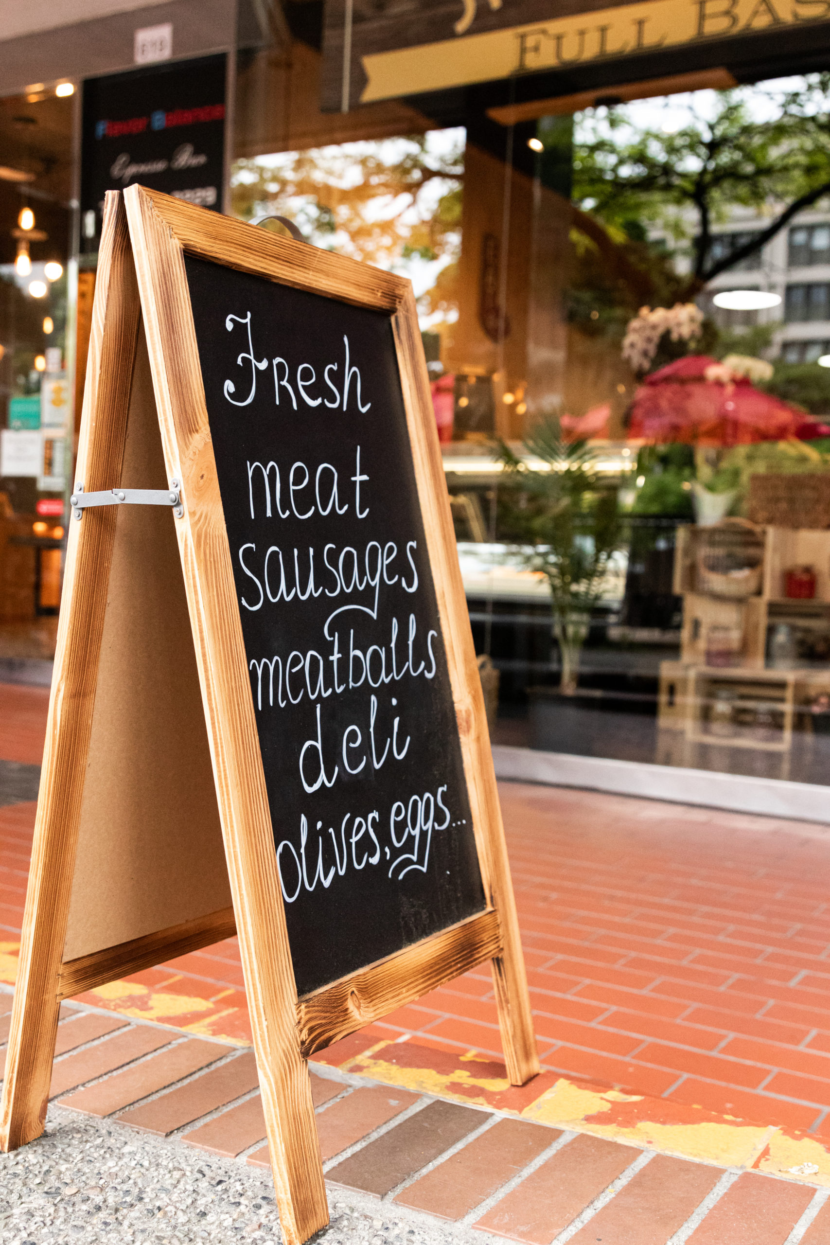 a chalk board outside a shop that advertises items for sale inside